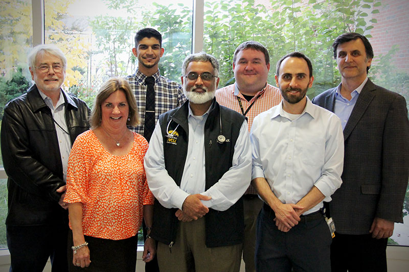 Dr. Amir Toor standing with a group of research collaborators